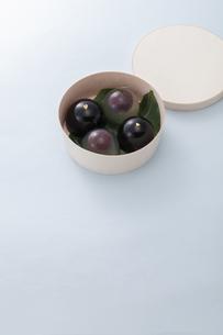 水色のテーブル上で丸い箱に入った和菓子の写真素材 [FYI04302087]