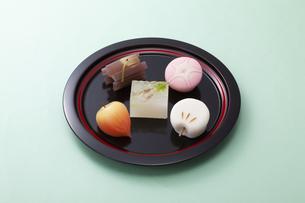 水色のテーブル上で黒いお皿に乗った和菓子の写真素材 [FYI04302089]