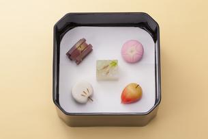オレンジのテーブル上で黒い重箱に入った和菓子の写真素材 [FYI04302115]