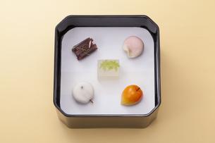 オレンジのテーブル上で黒い重箱に入った和菓子の写真素材 [FYI04302116]