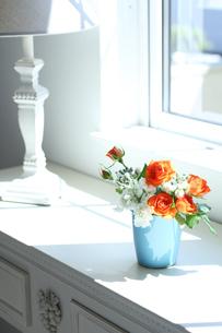オレンジ色のバラ・白いストックを青い器にアレンジ 窓辺に置いて(生花)の写真素材 [FYI04302508]