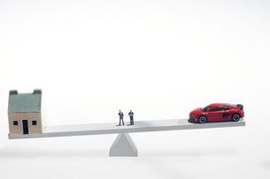 天秤に乗せた車とコインとミニチュア人形の写真素材 [FYI04302967]