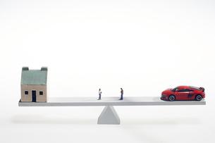 天秤に乗せた車と家と夫婦のミニチュア人形の写真素材 [FYI04302968]