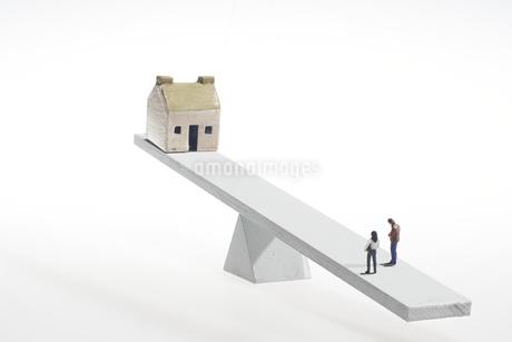 天秤に乗せた家と夫婦のミニチュア人形の写真素材 [FYI04302970]