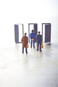 3つの扉の前に立つ3体のミニチュア人形の写真素材 [FYI04303013]