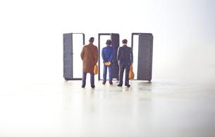 3つの扉の前に立つ3体のミニチュア人形の写真素材 [FYI04303014]