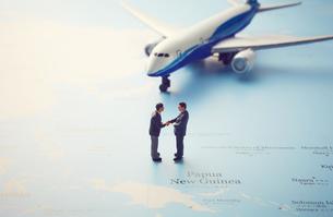 世界地図の上の飛行機と握手をするミニチュアの写真素材 [FYI04303026]
