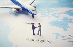 世界地図のアメリカの上で握手をするミニチュア人形と飛行機の写真素材 [FYI04303031]