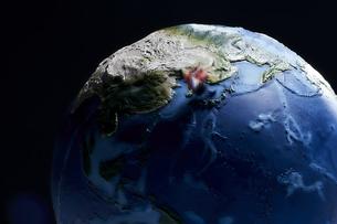 黒い背景に地球の模型と横切るミニチュア人形の写真素材 [FYI04303041]