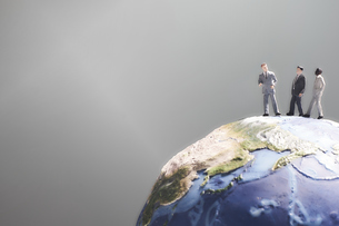黒い背景に地球の模型と歩きながら話し合うミニチュア人形の写真素材 [FYI04303053]