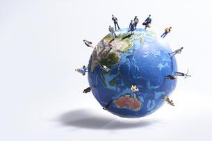 地球の模型の日本に向かって歩み寄るミニチュア人形たちの写真素材 [FYI04303068]