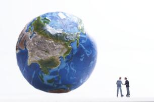 地球の模型の前で握手するミニチュアのサラリーマンの写真素材 [FYI04303078]