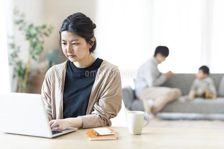 自宅でリモートワークをしている母と家族の写真素材 [FYI04303079]