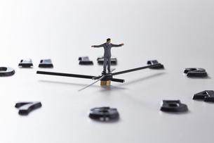 時計の針の上に乗るミニチュアのサラリーマンの写真素材 [FYI04303236]