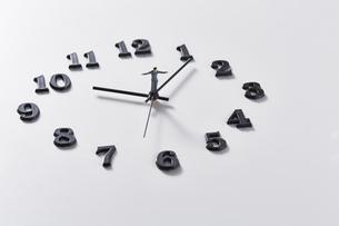 時計の針の上に乗るミニチュアのサラリーマンの写真素材 [FYI04303237]