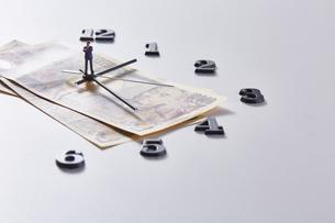 紙幣に置かれた時計の針の上に乗るミニチュアのサラリーマンの写真素材 [FYI04303238]