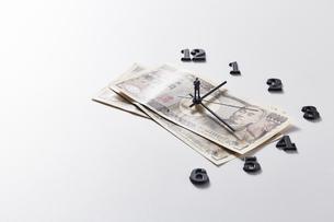 紙幣に置かれた時計の針の上に乗るミニチュアのサラリーマンの写真素材 [FYI04303239]