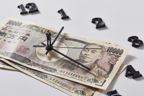 紙幣に置かれた時計の針の上に乗るミニチュアのサラリーマンの写真素材 [FYI04303241]