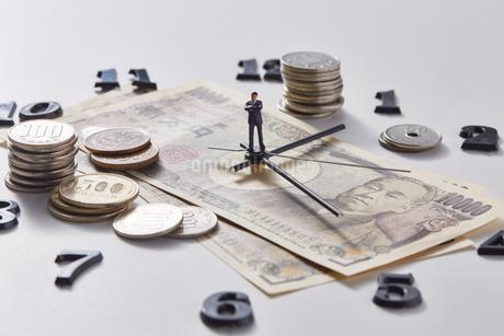 紙幣に置かれた時計の針の上に乗るミニチュア人形と硬貨の写真素材 [FYI04303242]