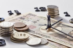 紙幣に置かれた時計の針の上に乗るミニチュア人形と硬貨の写真素材 [FYI04303243]