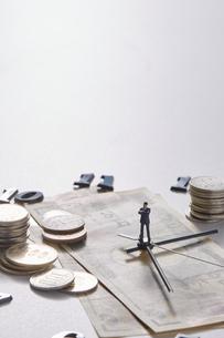 紙幣に置かれた時計の針の上に乗るミニチュア人形と硬貨の写真素材 [FYI04303244]