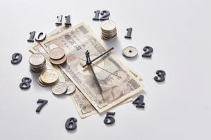 紙幣に置かれた時計の針の上に乗るミニチュア人形と硬貨の写真素材 [FYI04303245]