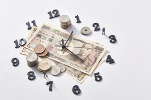 紙幣に置かれた時計の針とミニチュアのサラリーマンと硬貨の写真素材 [FYI04303246]