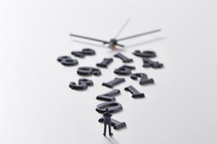 バラバラの数字と時計の針の前に立つミニチュア人形の写真素材 [FYI04303248]