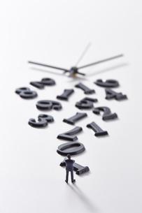 バラバラの数字と時計の針の前に立つミニチュア人形の写真素材 [FYI04303249]
