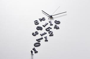 バラバラの数字と時計の針の前に立つミニチュア人形の写真素材 [FYI04303250]