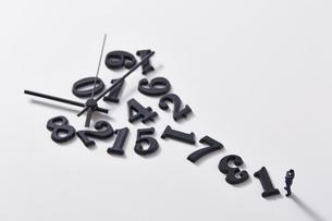バラバラの数字と時計の針の前に立つミニチュア人形の写真素材 [FYI04303252]