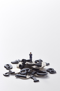 バラバラの数字と硬貨の上に立つミニチュア人形の写真素材 [FYI04303254]