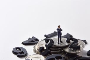 バラバラの数字と硬貨の上に立つミニチュア人形の写真素材 [FYI04303256]