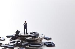 バラバラの数字と硬貨の上に立つミニチュア人形の写真素材 [FYI04303257]