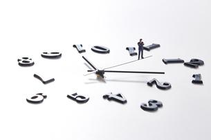 バラバラの数字と時計の針の上に乗るミニチュアのサラリーマンの写真素材 [FYI04303258]