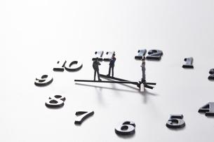 時計の針の上に乗るミニチュアのサラリーマンたち の写真素材 [FYI04303264]