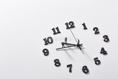 時計の針の上に乗るミニチュアのサラリーマンたち の写真素材 [FYI04303266]