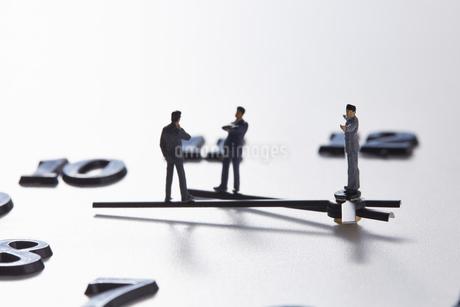 時計の針の上に乗るミニチュアのサラリーマンたち の写真素材 [FYI04303267]