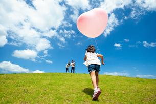 風船を持って駆け上がる女の子と家族の写真素材 [FYI04303324]
