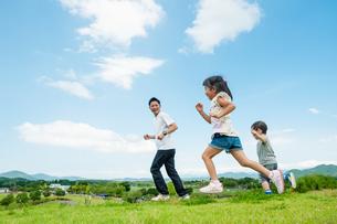 草原を走る二人の子供と父親の写真素材 [FYI04303329]