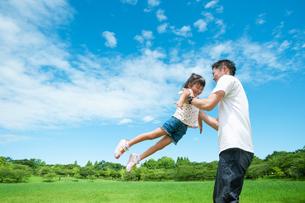 公園で高い高いをしてもらって喜ぶ女の子の写真素材 [FYI04303335]