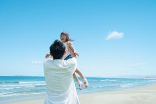海で高い高いをしてもらって喜ぶ女の子の写真素材 [FYI04303336]