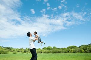 公園で高い高いをしてもらって喜ぶ男の子の写真素材 [FYI04303338]
