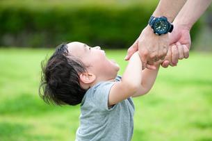 嬉しそうに父親の手につかまる男の子の写真素材 [FYI04303413]
