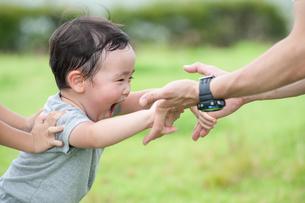 嬉しそうに父親の手につかまる男の子の写真素材 [FYI04303415]
