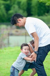父親と楽しそうに押し相撲をする姉弟の写真素材 [FYI04303416]