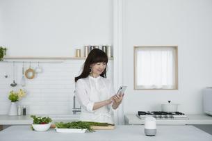 キッチンに立つ女性とスマートスピーカーの写真素材 [FYI04303719]