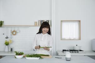 キッチンに立つ女性とスマートスピーカーの写真素材 [FYI04303720]