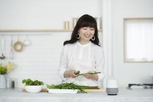 キッチンに立つ女性とスマートスピーカーの写真素材 [FYI04303724]