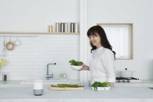 キッチンに立つ女性とスマートスピーカーの写真素材 [FYI04303725]
